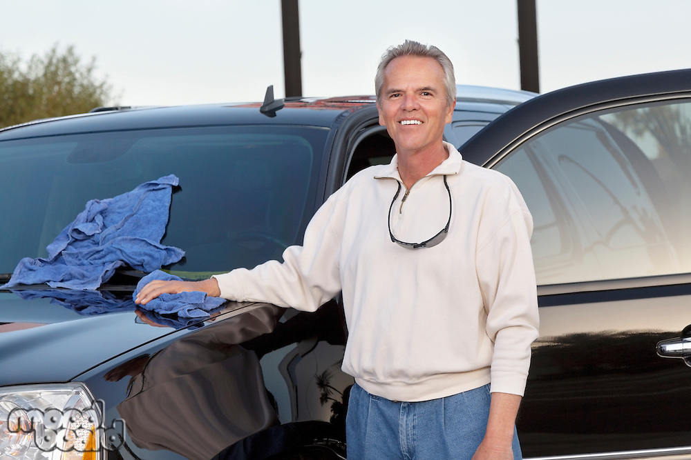 Portrait of mature man standing next to his car