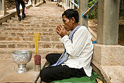 02 JULY 2006 - UDONG, CAMBODIA: A blind man prays on the steps leading to the top of the former royal citadel in Udong, Cambodia. The citadel now houses the grave sites of ancient Cambodian kings and is a revered place in Cambodia. Photo by Jack Kurtz / ZUMA Press