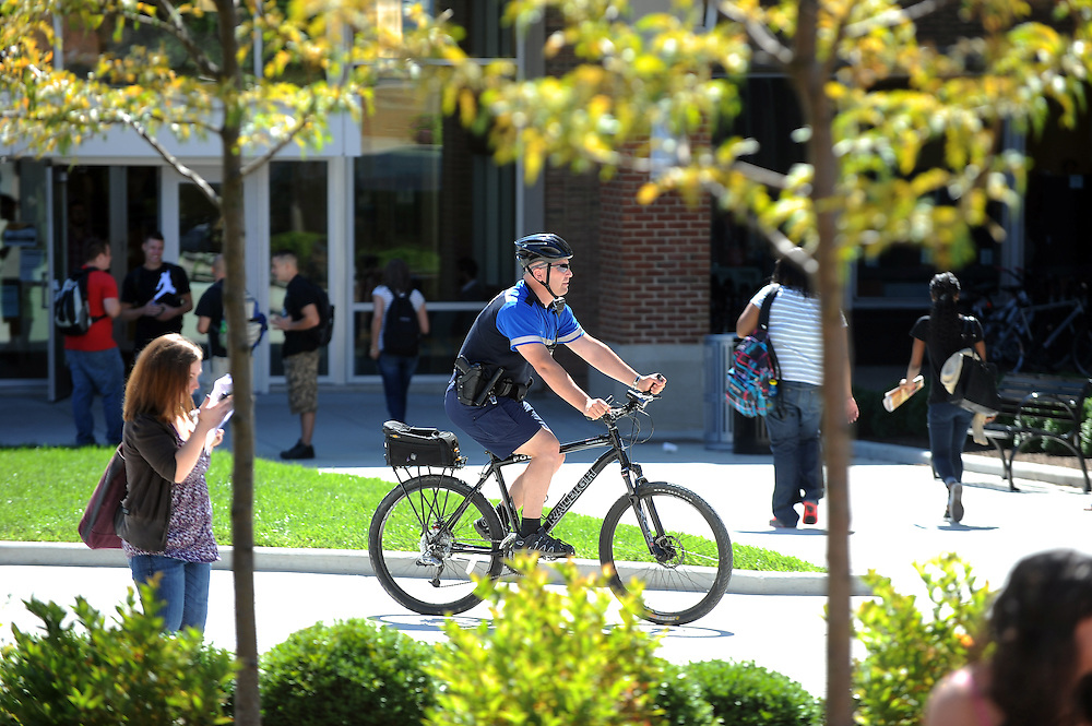 Jeff Futo, a member of the Kent State Police Department, rides a bike through the Risman Plaza while on day time patrol. Bikes are one of the easiest modes of getting from one end of campus to the other and are used by the police as the weather allows.