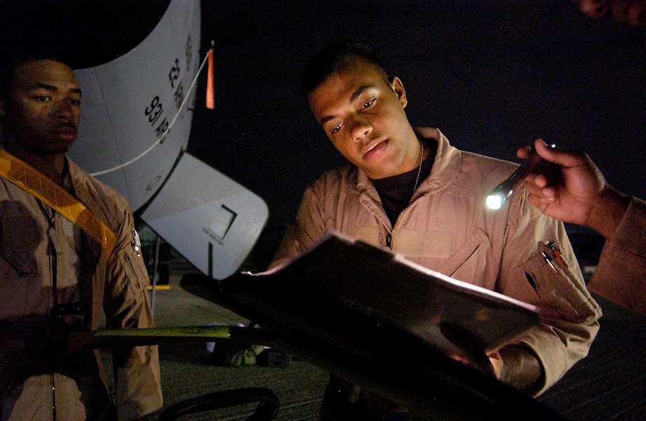 Captain Otis Hooper (right), mission commander, from Newport News, Va. and Staff Sergeant Eddie Johnson, boom operator, from Chicago, Ill., reviews the maintenance log book of their a KC-135R Stratotanker, before they begin a pre-dawn mission that will take them over Baghdad, Iraq. Captain Travis Diltz (holding flashlight), aircraft commander, and the others two are African-American.  By chance there were assigned together as a crew for the 908th Expeditionary Aerial Refueling Squadron.  The tight knit three-man crew takes pride and in this common fact and say they fly with the spirit of the Tuskegee Airmen.  (U.S. Air Force photo / Master Sgt. Lance Cheung)