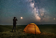 A Park interpreter poses for a scene in Grasslands National Park, Saskatchewan, of stargazing with binoculars under the Milky Way on a dark moonless night. Grasslands is perfect for stargazing as it is a Dark Sky Preserve and the horizon is vast and unobstructed. <br /> <br /> Mars is bright to the left and the galactic centre is to the south at right. The view is overlooking the Frenchman River Valley. <br /> <br /> This is a stack of 4 exposures for the ground and one untracked exposure for the sky, all 30 seconds at f/2.8 with the 20mm Sigma lens and Nikon D750 at ISO 6400. LENR was on.