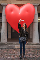 "© Licensed to London News Pictures. 14/02/2018. LONDON, UK. A tourist takes a selfie against a giant chubby heart balloon at Covent Garden as part of ""Chubby Hearts Over London"",  a design project conceived by Anya Hindmarch.  Supported by the Mayor of London, the British Fashion Council and the City of Westminster giant chubby heart balloons will be suspended over (and sometimes squashed within) London landmarks as a declaration of love to the city starting on Valentine's Day and continuing throughout London Fashion Week.   Photo credit: Stephen Chung/LNP"
