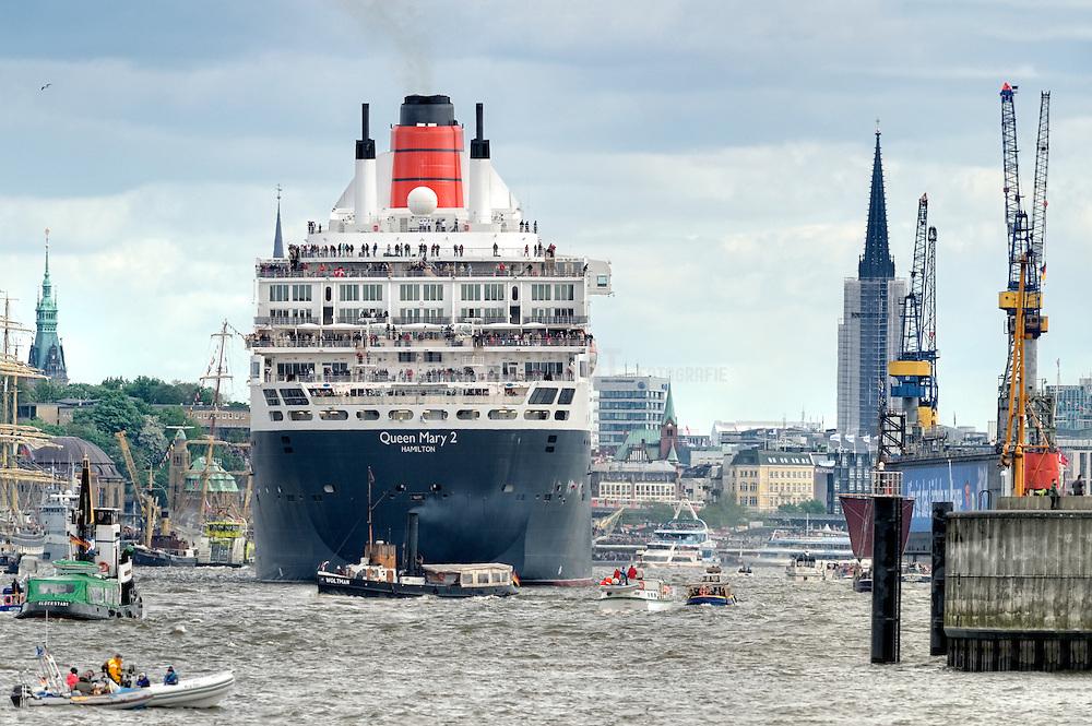 Die Queen Mary II läuft in den Hafen Hamburg ein und ist umringt von Barkassen. Im Hintergrund ist der Turm vom Rathaus und der Kirche St. Nikolai zu sehen.