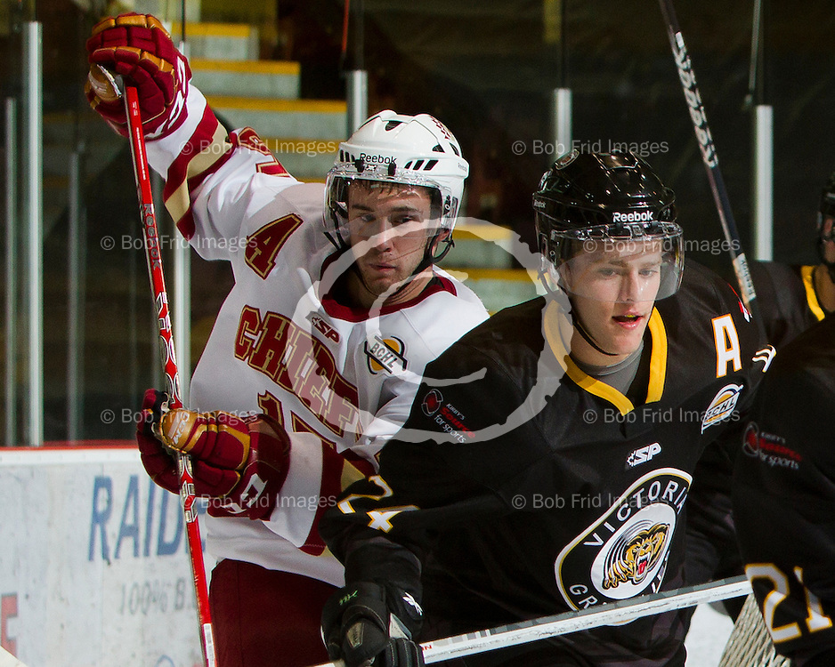 22 September 2012:  Josh Hansen (15) of the Chiefs ,DJ Jones (24) of the Grizzlies  during a game between the Chilliwack Chiefs and the Victoria Grizzlies at  Prospera Centre, Chilliwack, BC.    Final Score: Chilliwack 2  Victoria 4   ****(Photo by Bob Frid - All Rights Reserved 2012): mobile: 778-834-2455 : email: bob.frid@shaw.ca ****