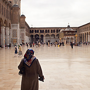 A woman, shoes in hand, stands looking at courtyard of Umayyad Mosque, Damascus