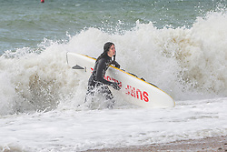 © Licensed to London News Pictures. 02/03/2019. Brighton, UK. Members of the Brighton Surf Life Saving Club brave the cold and powerful waves of the sea to go for a swim and surf in Brighton and Hove. Photo credit: Hugo Michiels/LNP