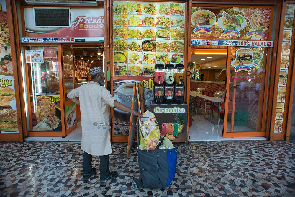 Roma, 24/06/2017: Indiano di fronte ad negozio di food asiatico take away, piazza Vittorio.<br /> &copy; Andrea Sabbadini