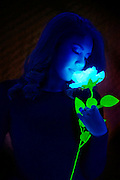 Woman smelling a glowing flower.Black light