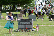 Hamptonburgh, NY - A young girl gets ready to place flowers at a veteran's grave during Memorial Day ceremonies at Hamptonburgh Cemetery on May 25, 2009. This was the 142nd year flowers have been placed at veterans' graves on Memorial Day, which was formerly known as Decoration Day.