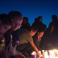 Alvera Begaye, right, lights a candle for Ashlynne Mike at the roadside memorial near mile marker 13 on Navajo Route 36 in San Juan Tuesday night. The memorial marks the area Ashlynne and her brother Ian Mike were abducted Monday after being dropped off by the school bus.