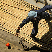 A deck department Sailor prepares to toss a heaving line from the foc'sle of the amphibious dock landing ship USS Fort McHenry (LSD 43) as the ship prepares to moor pierside in Salalah, Oman, for a scheduled port visit. .Fort McHenry is currently deployed with the Bataan Amphibious Ready Group (ARG) in support of Maritime Security Operations (MSO) in the U.S. 5th Fleet area of operations. MSO help set the conditions for security and security efforts of regional nations and seek to disrupt illegal use of the maritime environment as a venue for attack or to transport personnel, weapons or other material.
