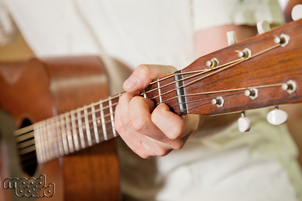 Close-up view of man's hand playing guitar