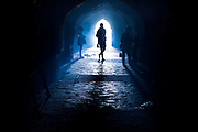 26th November 2015, New Delhi, India.  A woman is silhouetted in catacombs of the ruins of Feroz Shah Kotla in New Delhi, India on the 26th November 2015<br /> <br /> PHOTOGRAPH BY AND COPYRIGHT OF SIMON DE TREY-WHITE a photographer in delhi<br /> + 91 98103 99809. Email: simon@simondetreywhite.com<br /> <br /> <br /> The13th century fortress-city of Firoz Shah Kotla in Delhi is thronged weekly with thousands of supplicants seeking favour from supernatural beings of smokeless fire, - Djinns. These magical entities also known as Jinn, Jann or Genies spring from Islamic mythology as well as pre-Islamic Arabian mythology. They are mentioned frequently in the Quran and other Islamic texts and inhabit an unseen world called Djinnestan. Believers, mostly Muslim but from other faiths too, circumnavigate the ruins clutching dozens of photocopied requests, flower petals, incense, and candles. They visit the numerous niches and alcoves in the catacombs said to be occupied by different djinns and greet and salute the invisible occupants with offerings.  A copy of their requests, often with detailed contact information, photographs and even police reports to bolster the case is left with the 'Baba' before moving on to the next where the procedure is repeated - like making applications at different departments of a bureaucracy