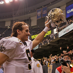 2009 October 18: New Orleans Saints quarterback Drew Brees (9) holds his helmet in the air as he runs off the field following a 48-27 win by the New Orleans Saints over the New York Giants at the Louisiana Superdome in New Orleans, Louisiana.