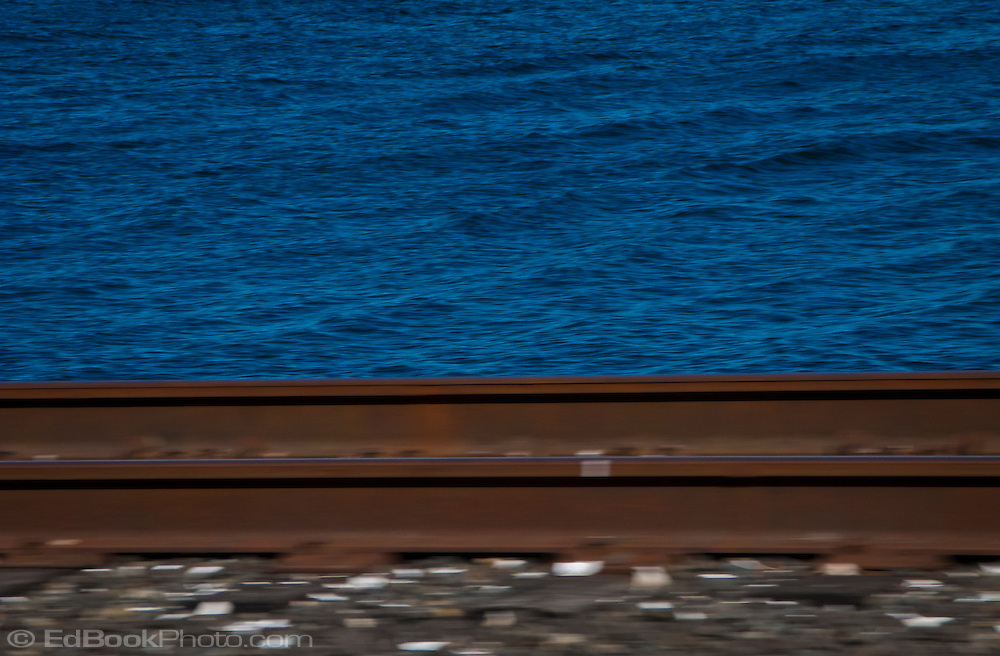motion blurred railroad rails against sharper farther away waves and ripples on Sinclair Inlet of Puget Sound, Washington, USA abstract