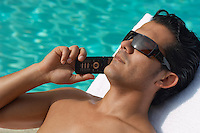 Man lying on sunlounger and talking on mobile phone, close-up