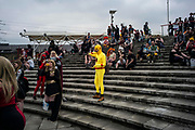 UNITED KINGDOM, London: 25 May 2018 (Left to right) A cosplay fan and his yellow outfit stands out of the crowd  outside of the MCM London Comic-Con this afternoon. The three day comic convention, which is held at London's ExCeL, will see thousands of visitors many of them in cosplay, dressed as their favourite super hero, villain or comic book character. Rick Findler  / Story Picture Agency