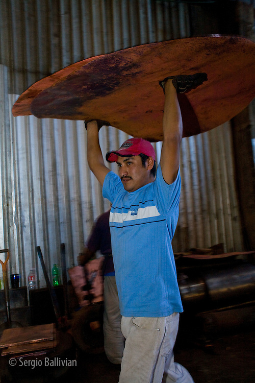 A worker carries copper sheets in a copper foundry in Santa Clara, Mexico.