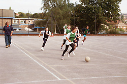 Secondary school pupils playing game of football during outdoor PE lesson,