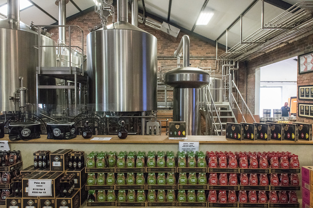Boxes of handcrafted beer sit in front of metal storage vats containing beer at microbrewery, Cape Town, South Africa