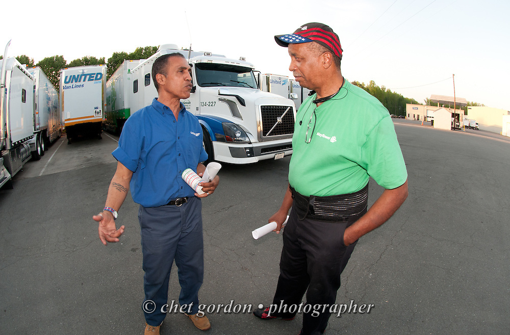 Over the road driver Jose Williams (left) speaks with a fellow driver in Stafford, VA on Monday May 4, 2015. Williams, a cross country trucker with a national household moving company, made the first of two delivery stops on the East Coast with loads that originated in California's Bay Area on April 27th.  © Chet Gordon/THE IMAGE WORKS