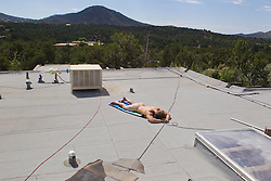 naked man getting sun on a rooftop in New Mexico
