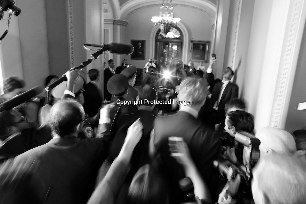 U.S. Senator Ted Cruz (R-TX) (C) is flanked by reporters and police as he departs after a Republican Senate caucus meeting at the U.S. Capitol in Washington, October 16, 2013. U.S. Senate leaders struck a bipartisan 11th-hour deal to break the fiscal impasse on Wednesday, and the Republican-led House of Representatives agreed to take it up as Congress moved to avert a historic debt default.