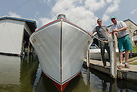 Seth and Gary Kiedaisch launched their 1952 27' Chris Craft  in Paugus Bay at Irwin Marine on Friday afternoon.  Theis semi-enclosed cruiser has been fully restored.  (Karen Bobotas/for the Laconia Daily Sun)