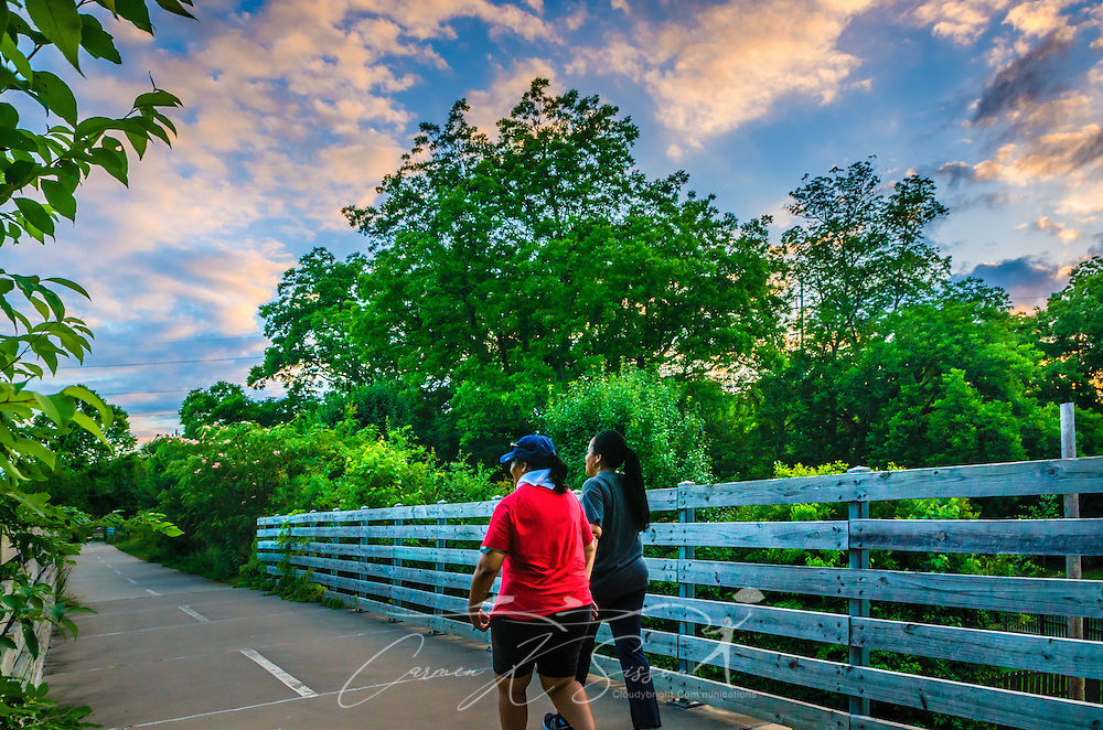 Walkers cross a bridge along the Stone Mountain Village walking trail, June 2, 2014, in Stone Mountain, Georgia. (Photo by Carmen K. Sisson/Cloiudybright)