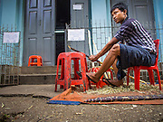 01 NOVEMBER 2014 - YANGON, MYANMAR: A man cuts sugar cane for snacks on a street in Yangon, Myanmar.    PHOTO BY JACK KURTZ