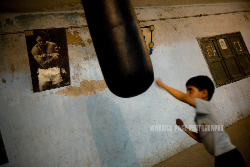 KARACHI, PAKISTAN - OCTOBER 12: A young boy attempts to train on a heavy bag at the Young Baloch Boxing Club, Sunday, October 12, 2008, in Karachi, Pakistan. Lyari is Karachi's poorest, most dangerous, drug and crime-infested slum, but has produced the bulk of Pakistan's champion boxers. Boxing has been a way of survival for many of the young men, who are often sponsored by corporations and event the military, to box for them at events throughout the city and the country. Lacking in the most basic resources, including a sufficient diet, the young boxers have watched countless champions on television throughout the years, attempting to emulate their abilities. (Photo by Warrick Page)