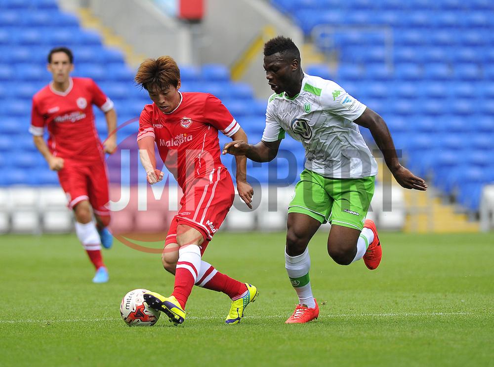 Cardiff City's Kim Bo Kyung battles for the ball with VfL Wolfsburg's Junior Malanda - Photo mandatory by-line: Joe Meredith/JMP - Mobile: 07966 386802 02/08/2014 - SPORT - FOOTBALL - Cardiff - Cardiff City Stadium - Cardiff City v VfL Wolfsburg - Pre-Season Friendly