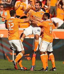 Adam Moffat #16 of the Houston Dynamo celebrates his goal in the nineteenth minute with teammate Jermaine Taylor #4 and Will Bruin #12 during the first half of a MLS Eastern Conference Semifinal against Sporting Kansas City November 4, 2012 at BBVA Compass Stadium in Houston, Texas.