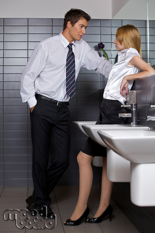 Young business couple talking intimately in office washroom