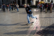 A skateboarder pushes off through reflected light outside the Church of St Mary on Rynek Glowny market square, on 22nd September 2019, in Krakow, Malopolska, Poland.