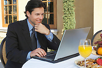 Mid adult business man working on laptop at outdoor cafe table