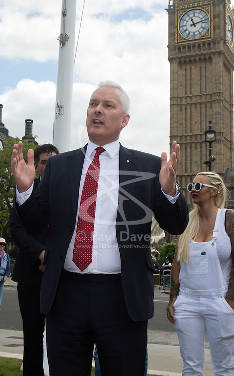"Westminster, London, May 24th 2016. Animal rights protesters from ""Boycott Dogs4Us"" protest outside Parliament against puppy farming and third party puppy selling as the Environment, Food and Rural Affairs Sub-Committee are investigating the sale of dogs as part of their animal welfare inquiry. PICTURED: SNP MP Paul Monaghan addresses the crowd."