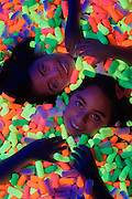 Two young smiling girls lying down in a pile of glowing packing peanuts.Black light