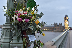 © Licensed to London News Pictures. 22/03/2018. LONDON, UK.  Floral tributes on Westminster Bridge. A projection at dusk of the words #LondonUNITED will be seen on the Houses of Parliament on the first anniversary of the Westminster terror attack.  The projection is part of the #LondonUNITED tribute initiative by the Mayor of London to the victims in the terror attacks in the capital in 2017.  Similar projections will take place on the first anniversary of the terror attacks which took place at London Bridge, Finsbury Mosque and Parsons Green.  Photo credit: Stephen Chung/LNP