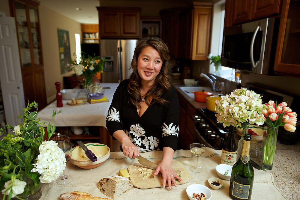 Kim Sunée chopping hazelnuts for her Cheese and Thyme Pots de Crème from her new book, A Mouthful of Stars, to be released on May 6, 2014. In her home kitchen in Anchorage, AK on April 28, 2014. <br /> <br /> CREDIT: Ash Adams for the Wall Street Journal. <br /> IMKSUNEE.OD
