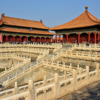 Two Great Halls in Outer Court at Forbidden City in Beijing, China <br /> Sharing the elevated, Outer Court platform with the Hall of Supreme Harmony are two additional structures. Collectively, they are called the Three Great Halls. On the right is the Hall of Central Harmony. The single-eave, square-shaped pavilion was originally called the Hall of the Splendid Canopy (Huagai dian) when constructed in the early 15th century. The Ming dynasty emperors used the facility as a staging area before imperial ceremonies. Zhonghe dian was rebuilt in 1627. Adjacent is the Hall of Preserving Harmony. The emperor used Baohe dian to dress and prepare for receiving homage by quest. Most impressive is the three-tiered staircase leading up to the halls.