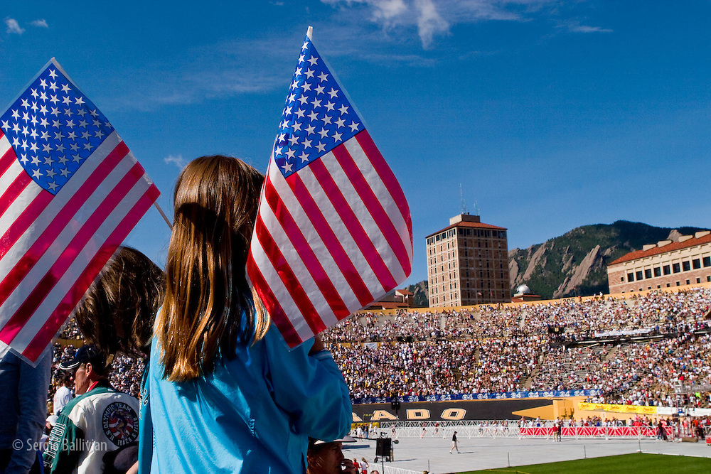 A young girl holds two American flags in McMahon Stadium on the campus of the University of Colorado Boulder as she looks at runners ending the BoulderBolder 10K race in Boulder, Colorado.