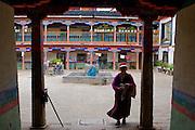 A woman walks in an apartment courtyard, near the Jokhang Monastery in Lhasa, Tibet.