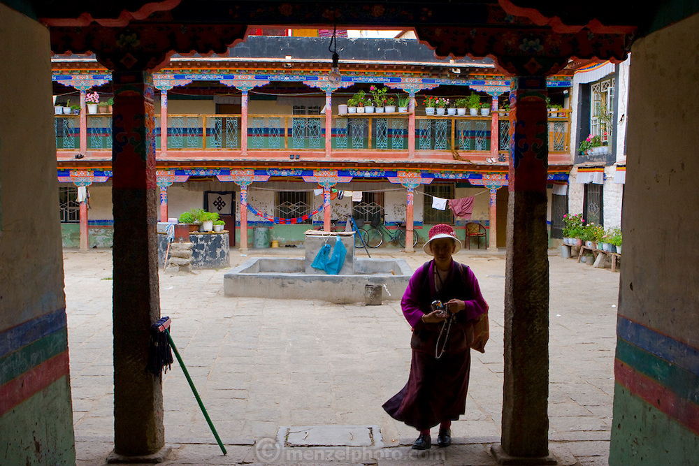 A woman walks in an apartment courtyard, near the Jokhang Monastery in Lhasa, Tibet.