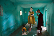 """A Buddhist monk meditates in prayer at one of the thousands of shrines in Amarapura, Burma's """"deserted city""""."""