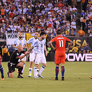 EAST RUTHERFORD, NEW JERSEY - JUNE 26: Lionel Messi #10 of Argentina picks up Brazilian referee Heber Lopes after they collided during the Argentina Vs Chile Final match of the Copa America Centenario USA 2016 Tournament at MetLife Stadium on June 26, 2016 in East Rutherford, New Jersey. (Photo by Tim Clayton/Corbis via Getty Images)