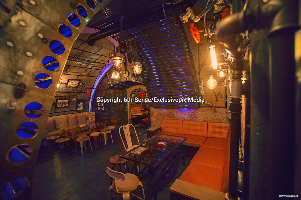 A night out that's 20,000 leagues under the sea: Romanian submarine bar complete with torpedoes and radar systems takes clubbers on a journey into the deep<br /> <br /> With it's nautical navigation charts and torpedoes mounted on the ceiling, at first glance this could be a Cold War submarine, patrolling the deep.<br /> But look a little closer and the control desk where a commander might fire a missile from is in fact a DJ booth, while underneath the pressure gauges and periscopes sit tables and bar stools. <br /> New theme bar Submarine is bringing a little of the ocean to land-locked Cluj-Napoca, Romania's second largest city after capital Bucharest, offering revellers a deep sea drinking experience.<br /> The bar is the brainchild of Romanian design company, 6th-Sense Interiors - who previously created a Jules Verne theme pub Joben Bistro in the city - and is split into two vault-shaped rooms, each with its own bar, as well as details found on many a submarine, such as control panels, visible pipes, bolted metal doors, an engine-powered propeller and two torpedoes which are attached to the ceiling.<br /> ©6th-Sense/Exclusivepix Media