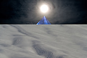albedo: dream landscape with snow on sloping field, rising blue pyramid on black horizon with sun on its summit and light reflections on surrounding clouds.