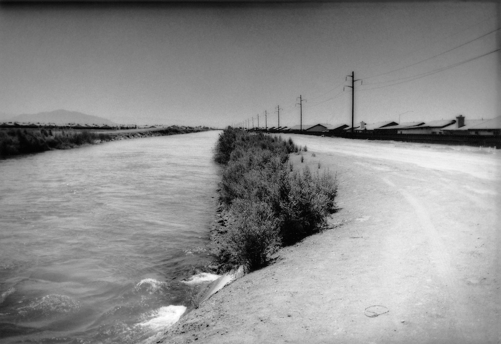All-American Canal passes new suburban housing development in the desert border town of Calexico.  Because land prices are more reasonable in the Imperial Valley, where summer temperatures can easily exceed 110 degrees F  (43 degrees C), is attracting new residents, putting even greater pressure on the limited water supplies.