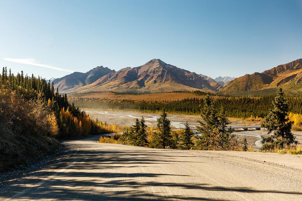 Denali Park Road as it approaches the Teklanika River in Denali National Park in Interior Alaska. Autumn. Morning.